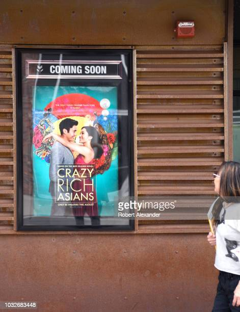 A poster displayed outside a movie theater advertises a coming attraction the film 'Crazy Rich Asians'