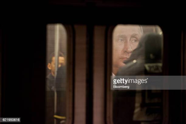 A poster displaying an image of Vladimir Putin Russia's president is seen through a subway car window in the Wall Street subway station in New York...
