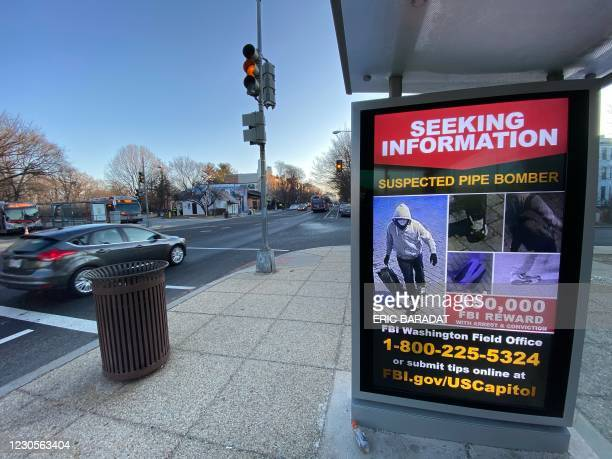 Poster distributed by the FBI seeking information on violent US President Donald Trump supporters, is seen displayed at a bus stop kiosk on a...
