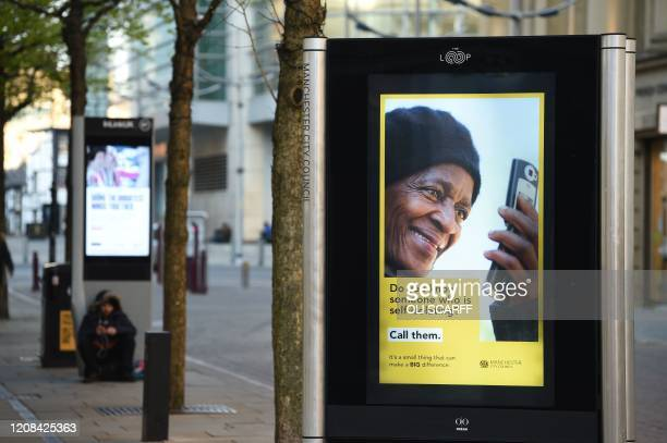 Poster encouraging people to contact those who are self-isolating is pictured in a near deserted central Manchester, north west England on March 27,...