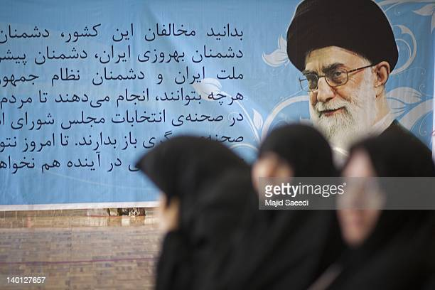 A poster featuring the picture of Iran's Supreme Leader Ayatollah Khamenei is passed by Iranian women outside Ali Zakani's main campaign headquarters...