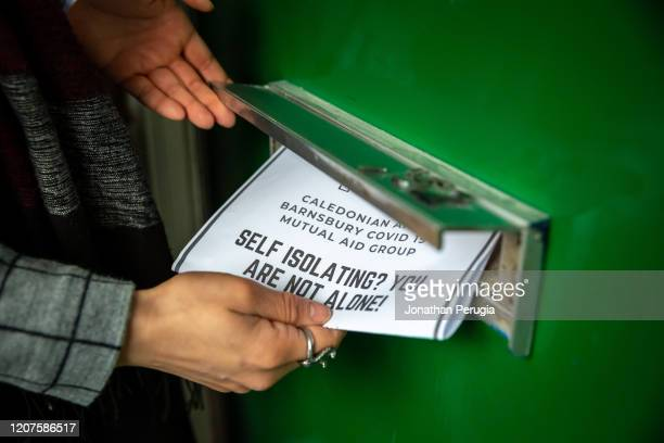 A poster for a community support group called Mutual Aid is posted through a letter box on a housing estate near the Caledonian Road in North London...