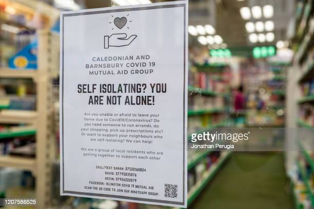 A poster for a local community support group called Mutual Aid is displayed in the window of a pharmacy on the Caledonian Road in North London on...