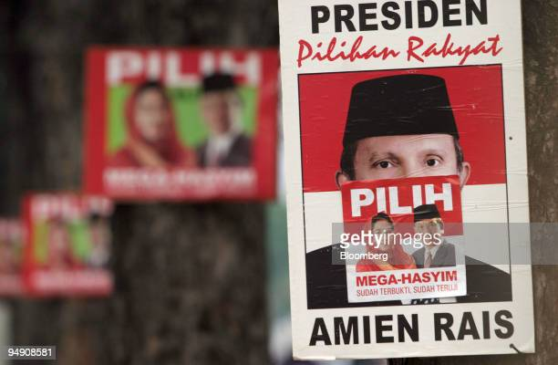 A poster for People's Consultative Assembly candidate Amien Rais has been pasted over with one for Indonesian President Megawati Soekarnoputri on a...