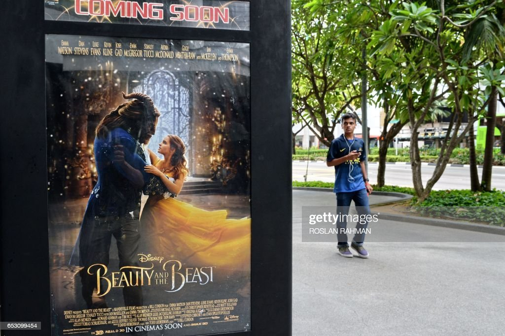 A poster for the film 'Beauty and the Beast' is displayed in Singapore on March 14, 2017. The film has come under fire from religious figures in Singapore, with Christian clergy attacking Disney for deviating from 'wholesome, mainstream values'. / AFP PHOTO / Roslan RAHMAN