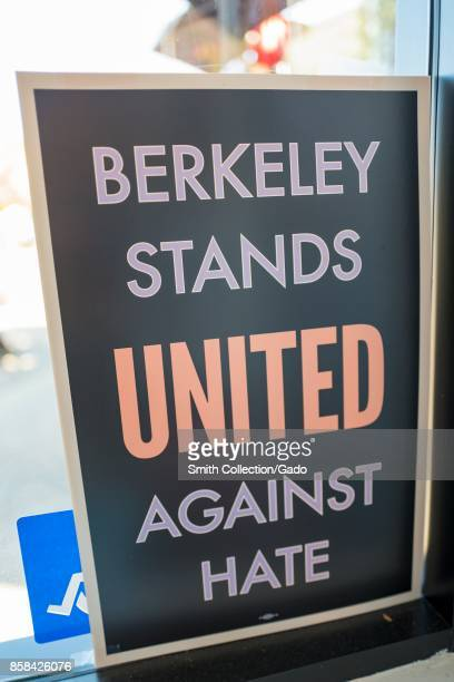 Poster in a shop window in Berkeley California reading Berkeley Stands United Against Hate part of a cityled response to alt right organizations'...