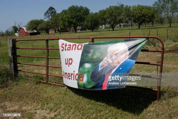 Poster in support of former President Trump hangs on a farm gate on April 10 in Colfax, Louisiana. Colfax was the site of a racial massacre that...