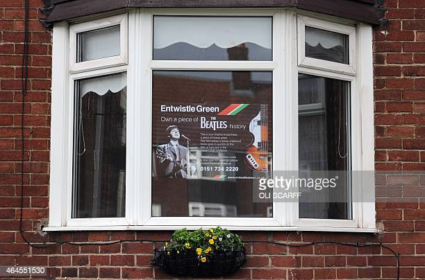 A poster in the window of the midterrace house at 72 Western Avenue in Speke the childhood home of British musician Paul McCartney is pictures before...