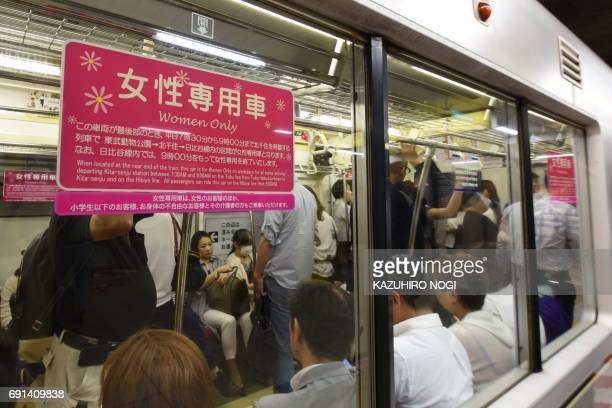A poster informing commuters of a women'sonly carriage is displayed on a subway train in Tokyo on June 2 2017 In Japan where train travel can often...