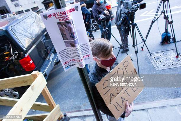 Poster of a suspect hangs from a post as a man holds a placard after an Asian American anti-violence press conference on March 30 outside the...