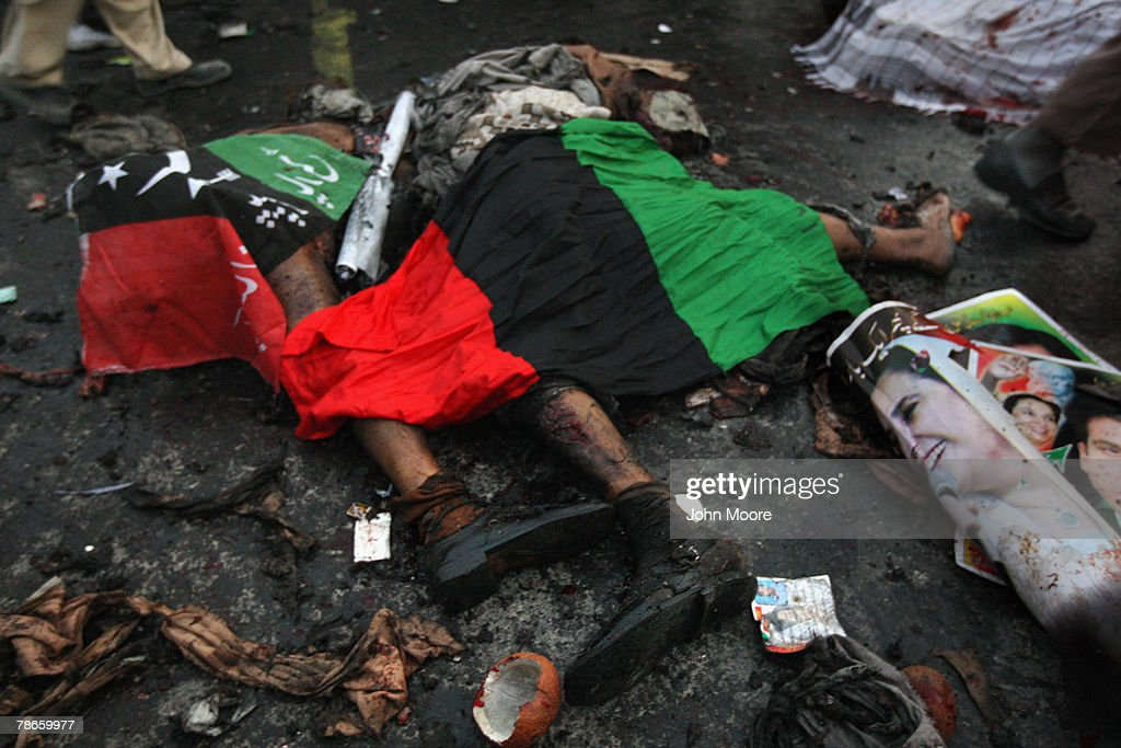 A poster of assassinated former Prime Minister Benazir Bhutto lies next to bomb blast victims covered in flags of Bhutto's Pakistan People's Party on December 27, 2007 in Rawalpindi, Pakistan. The opposition leader has died from wounds to the neck and head after speaking at an election rally in the northern city where an estimated 15 people were left dead by the explosion, a party official and Bhutto's husband have been quoted as saying.