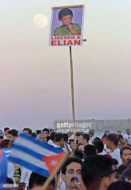 Poster of Cuban child Elian Gonzalez is held in the air during a demonstration near the Office of US interests in Havana 21 December 1999. Un retrato...