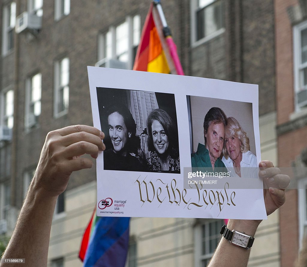 A poster of Edie Windsor, plaintiff in United States v. Windsor case, and her female spouse Thea Spyer, is held above the crowd gathered outside Stonewall June 26, 2013 in New York. A large group gathered to celebrate the Supreme Court ruling on the Defense of Marriage Act. AFP PHOTO/Don Emmert