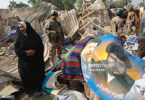 A poster of firebrand Shiite cleric Muqtada alSadr is pulled from the rubble in the aftermath of a double suicide car bomb attack that struck...