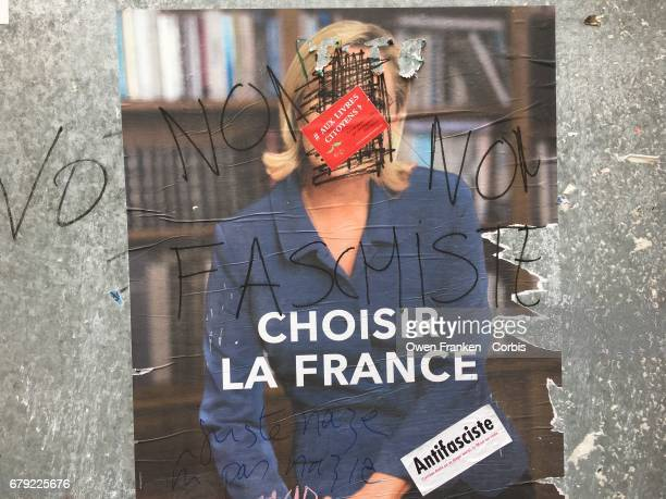 A poster of French presidential candidate Marine Le Pen is displayed covered with antifascist graffiti in front of a voting place in the 19th...
