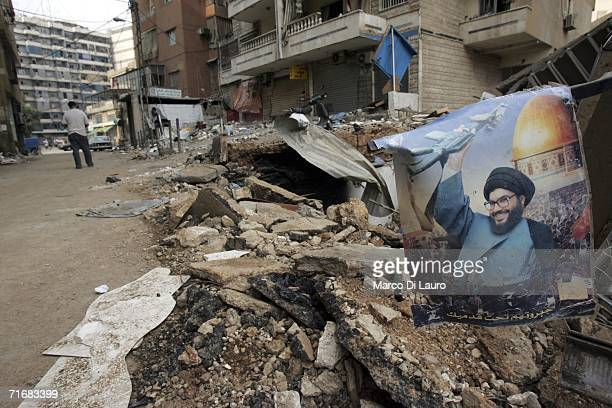 Poster of Hezbollah leader Hassan Nasrallah is seen next to buildings laying destroyed from Israeli airstrikes during the conflict between Hezbollah...