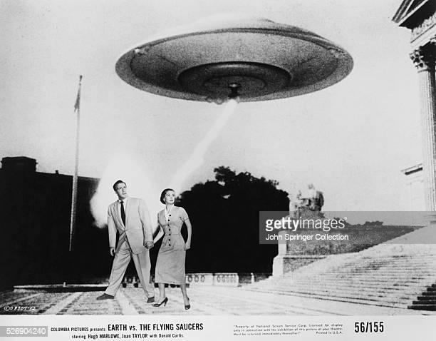 Poster of Hugh Marlowe and Joan Taylor walking below an alien spacecraft in the movie, Earth vs. The Flying Saucers.