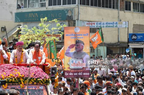A poster of Indian Prime Minister Narendra Modi is hold by a political supporter as Bharatiya Janata Party President Amit Shah participates in a road...