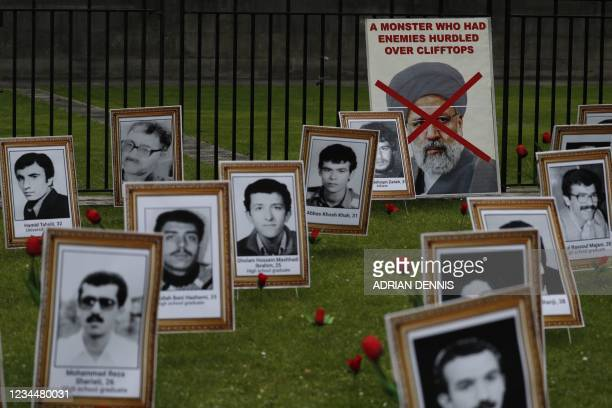 Poster of Iran's new president Ebrahim Raisi is seen next to portraits of people executed in 1988 following political uprising in Iran during a...