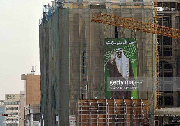 A poster of King Abdullah bin Abdul Aziz hangs from a building under construction with the slogan 'Thank God for your safety' in the Saudi capital...