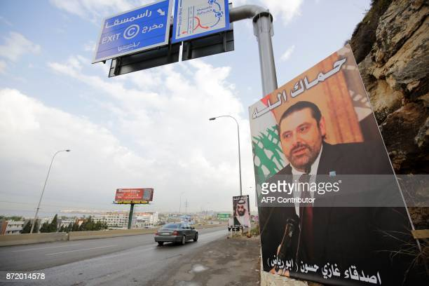 A poster of Lebanese Prime Minister Saad Hariri who resigned last week in a televised speech hangs on the side of a road with a phrase reading in...