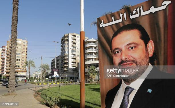 A poster of Lebanese Prime Minister Saad Hariri who resigned last week in a televised speech airing from the Saudi capital Riyadh hangs on the side...