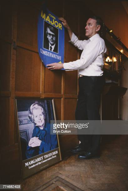 A poster of new Prime Minister and Conservative party leader John Major replaces a portrait of his predecessor Margaret Thatcher at Conservative...