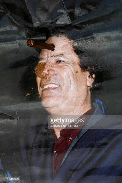 A poster of ousted Libyan strongman Moamer Kadhafi is torn by a bullet placed on his head by Libyan National Transitional Council fighters on the...