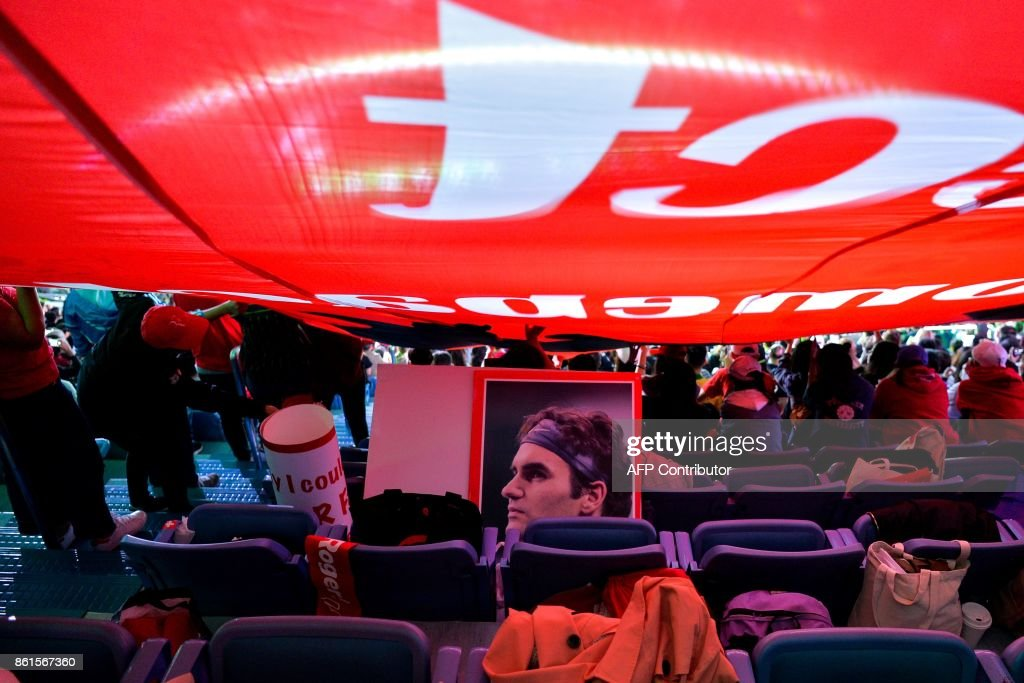 A poster of Roger Federer of Switzerland is seen on a chair under a huge flag waved by his fans during the men's singles final match against Rael Nadal of Spain at the Shanghai Masters tennis tournament in Shanghai on October 15, 2017. / AFP PHOTO / Chandan KHANNA