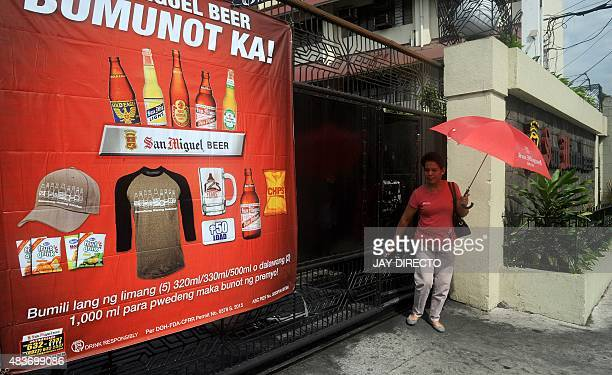 A poster of San Miguel beer products is posted at the gate at a warehouse as a women leaves the aria in Manila on August 12 2015 Top Philippine...
