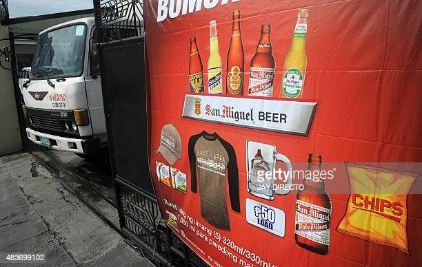 A poster of San Miguel beer products is posted at the gate of warehouse as a delivery truck leaves the aria in Manila on August 12 2015 Top...