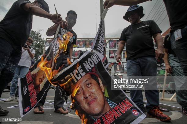 A poster of suspect Andal Ampatuan Jr is set on fire during a protest outside the presidential palace in Manila on November 23 to commemorate the...