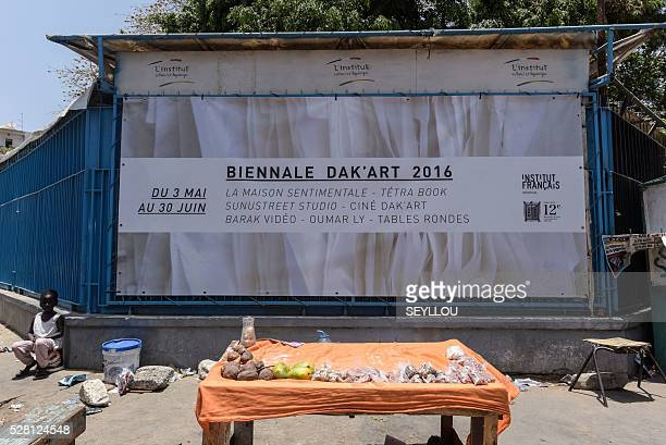 A poster of the biennale of contemporary African art hangs behind a fruit stall in Dakar on May 3 2016 / AFP / SEYLLOU