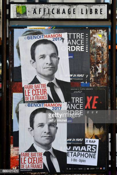 A poster of the candidate for the Socialist Party of France Benoit Hamon covers up a poster of Front National leader Marine Le Pen next to a bus...