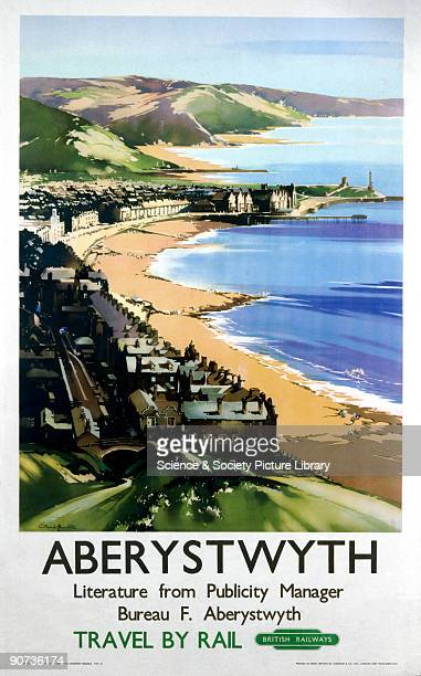 Poster produced for British Railways to promote rail travel to Aberystwyth, Ceredigion, Wales. The poster shows a view of the coast, with houses...