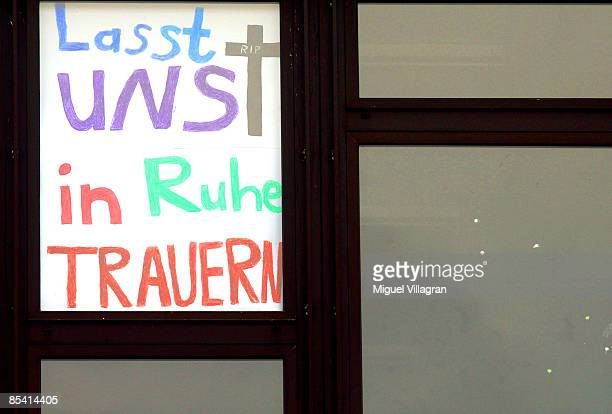 A poster reading 'Let us mourn in peace' is pictured in a window of a high school next to the Albertville School Centre on March 13 2009 in Winnenden...
