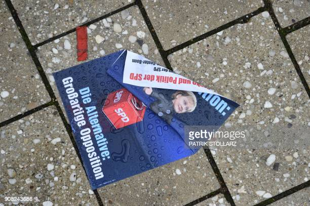 A poster reading 'The Alternative Wonderful Opposition' lays on the rainslicked pavement in front of the venue of an extraordinary congress of...