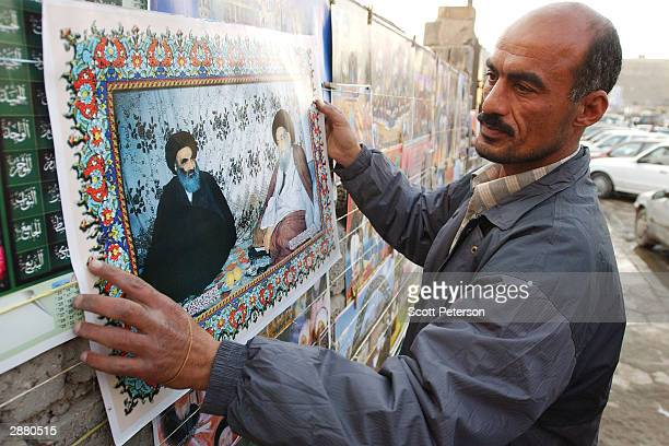Poster seller hangs a picture of Grand Ayatollah Ali Sistani, Iraq's pre-eminent Shiite Muslim cleric, meeting with his former teacher, Grand...