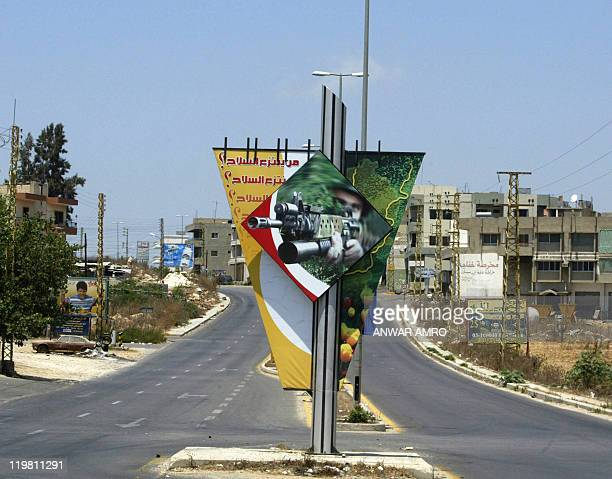 A poster showing a Hezbollah fighter is seen on the road in the southern Lebanese town of Deir alZahrani north of Nabatiyeh 31 July 2006 as Israel...
