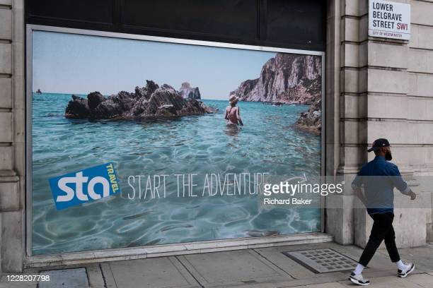 A poster showing a utopian beach is seen outside the Victoria offices of international budget flight and holiday booking service STA Travel whose...
