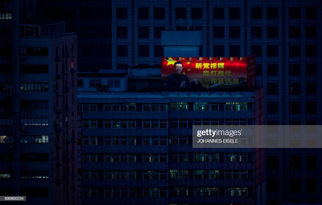 TOPSHOT - A poster showing China's President Xi Jinping is pictured on a high-rise building in downtown Shanghai on March 12, 2018. China's Xi Jinping on March 11 secured a path to rule indefinitely as parliament abolished presidential term limits, handing him almost total authority to pursue a vision of transforming the nation into an economic and military superpower. / AFP PHOTO / Johannes EISELE