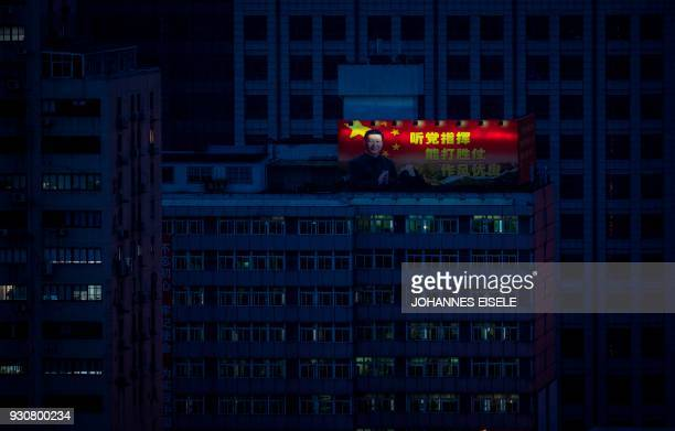 TOPSHOT A poster showing China's President Xi Jinping is pictured on a highrise building in downtown Shanghai on March 12 2018 China's Xi Jinping on...