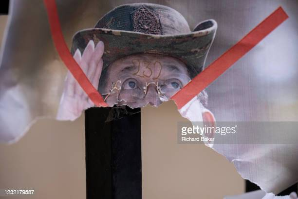 Poster showing de-facto leader of Myanmar's military government, General Min Aung Hlaing is torn in half on railings outside the country's London...