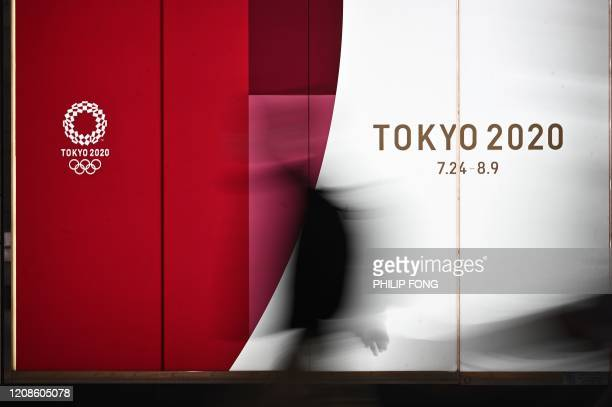 A poster showing the original planned date of the Tokyo 2020 Olympic Games is seen in a subway station in Tokyo on March 30 2020 Postponed Tokyo...