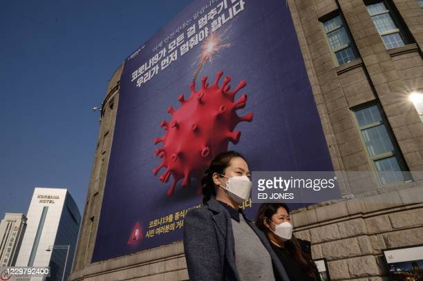 Poster warning against the covid-19 novel coronavirus is displayed in Seoul on November 26, 2020. - South Korea reported its highest daily number of...