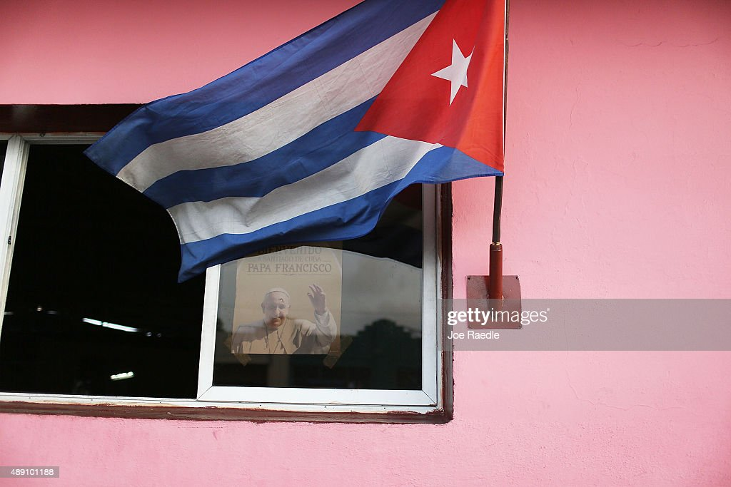 A poster welcoming Pope Francis is seen in a window near a Cuban flag as Cuba prepares for the pontiff's visit on September 19, 2015 in Santiago de Cuba, Cuba. Pope Francis is due to arrive in Havana, Cuba today for a three day visit where he will meet President Raul Castro and hold Mass in Revolution Square before travelling to Holguin, Santiago de Cuba and onwards to the United States.