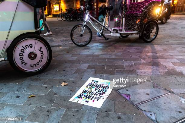Poster with a note 'To Remind You Where and Why' lies on a sidewalk by a rickshaws of Oxford Street as Coronavirus lockdown eases in London, England,...