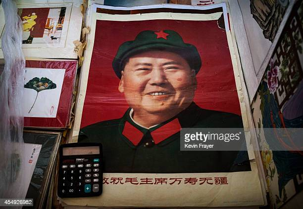 A poster with a portrait of the late Chinese leader Mao Zedong is seen for sale at a vendor's stand at a market on September 7 2014 in Beijing China...