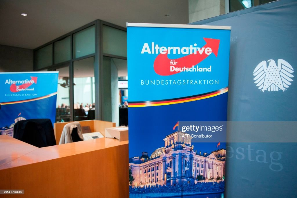 A poster with AfD logo is pictured next to a Bundestag background banner in front of parliamentary group room where the first meeting of the hard-right Alternative for Germany (AfD) party, at the Marie-Elisabeth-Lueders-Haus parliamentary building in Berlin on September 26, 2017, two days after general elections. /