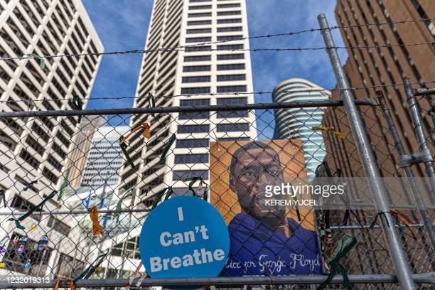 """Poster with George Floyd's picture and a sign reads that """"I can't Breathe"""" hang from a security fence outside the Hennepin County Government Center..."""